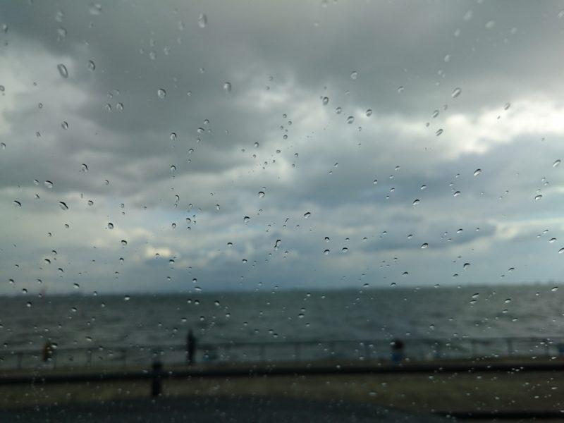 車のフロントウインドウに雨がまとわりつく